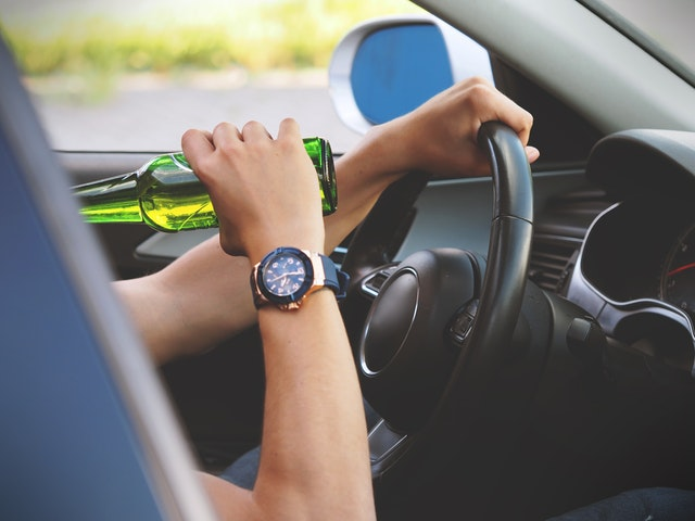 image of adult driving while drinking